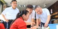 图为5月17日,省长沈晓明来到省残疾人创业就业一条街,向正在工作的残疾人问好,关切地询问他们的工作生活情况。 - 残疾人联合会