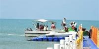 游客在天涯海角游览区游玩水上项目。 三亚日报记者 陈聪聪 摄 - 中新网海南频道