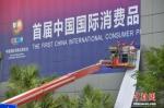 资料图:工作人员在海南国际会展中心外粘贴巨型主题宣传广告。中新社记者 骆云飞 摄 - 中新网海南频道